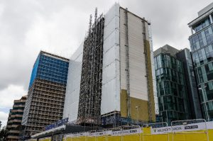 Scaffolding around a tall building in a busy city.